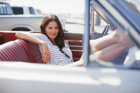 Smiling woman sitting in convertible - CAIF00672