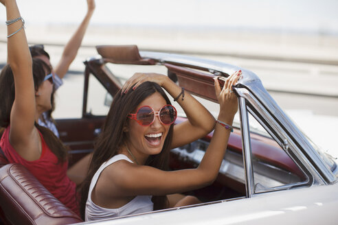 Smiling women driving convertible - CAIF00681
