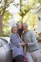 Older couple and granddaughter leaning on car - CAIF00714
