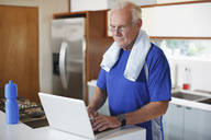 Older man using laptop after workout - CAIF00729