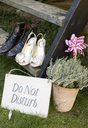 Newlywed couple's shoes with 'do not disturb' sign - CAIF00753