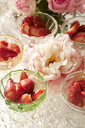 Bowls of strawberries and flowers on table - CAIF00765