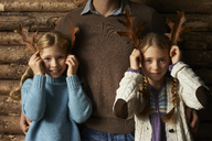 Girls using leaves as antlers with father - CAIF00855