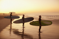Surfers holding boards on beach - CAIF00864