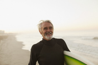 Older surfer carrying board on beach - CAIF00867