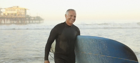 Older surfer carrying board on beach - CAIF00873
