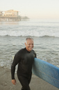 Older surfer carrying board on beach - CAIF00876