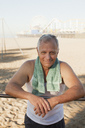 Older man relaxing after workout on beach - CAIF00879
