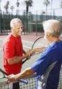 Older men shaking hands on tennis court - CAIF00882
