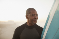 Older surfer carrying board on beach - CAIF00885