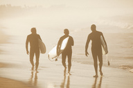 Older surfers carrying board on beach - CAIF00894