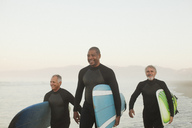 Older surfers carrying boards on beach - CAIF00897
