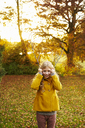 Girl holding branches like antlers - CAIF00900