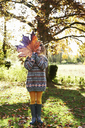 Girl playing with autumn leaf outdoors - CAIF00903