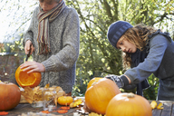 Children carving pumpkins together outdoors - CAIF00915