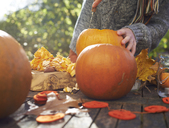 Teenage boy carving pumpkins outdoors - CAIF00930