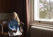 Girl using digital tablet in armchair - CAIF00933