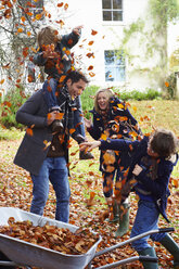 Family playing in autumn leaves - CAIF00939