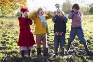 Children covering their ears as boy plays trumpet - CAIF00957