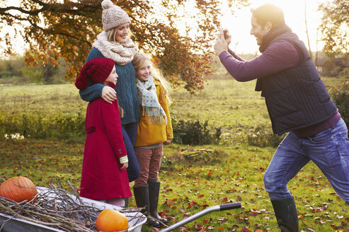 Father taking picture of family outdoors - CAIF00975