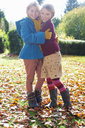 Girls hugging in autumn leaves - CAIF00978