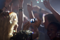 Woman with camera phone photographing friends on dance floor of nightclub - CAIF01050