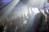 Crowd with arms raised behind railing at concert - CAIF01053