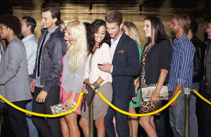 Couple with cell phone standing in queue outside nightclub - CAIF01059