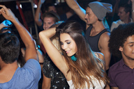 Confident woman dancing in crowd at nightclub - CAIF01065
