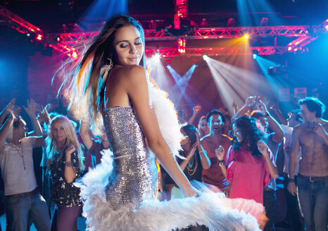 Woman in silver dress with feather boa dancing in nightclub - CAIF01068