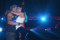 Smiling couple hugging under spotlights in nightclub - CAIF01098