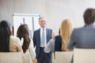Business people applauding businessman standing at flipchart - CAIF01137