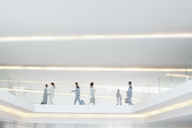 Business people walking along elevated walkway in airport - CAIF01146