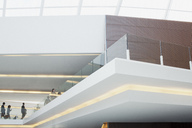 Business people with suitcases on elevated walkway - CAIF01152