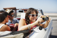 Smiling woman taking picture from convertible - CAIF01158