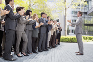 Crowd of business people cheering for businessman - CAIF01188