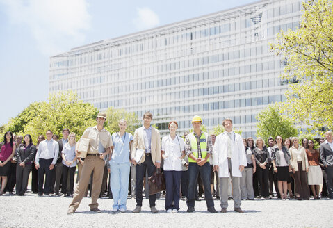 Portrait of professionals and workers with crowd of business people in background - CAIF01191