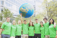 Portrait of team in green t-shirts lifting globe overhead - CAIF01197