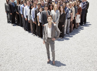 Portrait of confident businesswoman with team of business people in background - CAIF01224