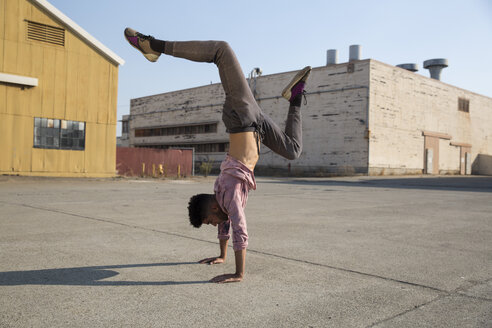 Young man doing a handstand outdoors - SUF00463