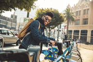 Stylish young man on the street with rental bike - SUF00472