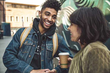 Happy young man and woman with coffee talking in the city - SUF00475