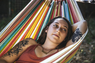 Portrait of young woman with tattoo lying in hammock - SUF00484