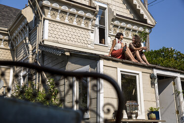 Two young women sitting on roof - SUF00487