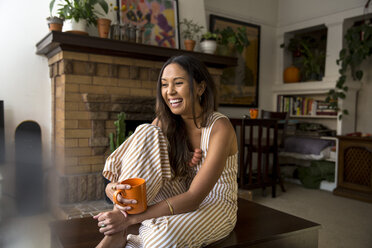 Laughing young woman with coffee mug sitting at home - SUF00490