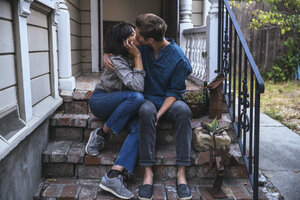 Couple sitting on stoop kissing - SUF00511
