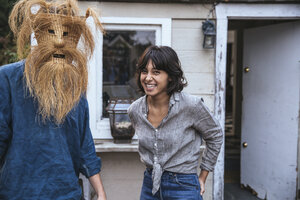 Man wearing funny mask and woman laughing - SUF00514