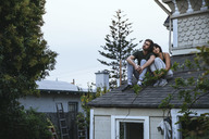 Relaxed couple sitting on roof - SUF00517