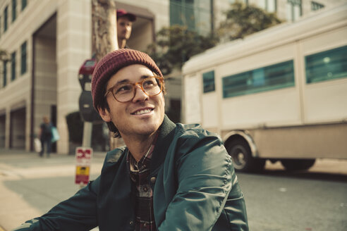 Portrait of stylish young man sitting on sidewalk - SUF00526