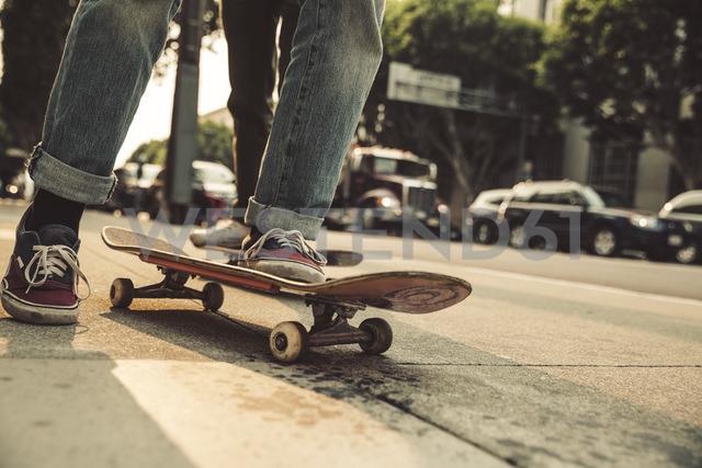 Close-up of man with skateboard on sidewalk - SUF00529 - Sullivan/Westend61